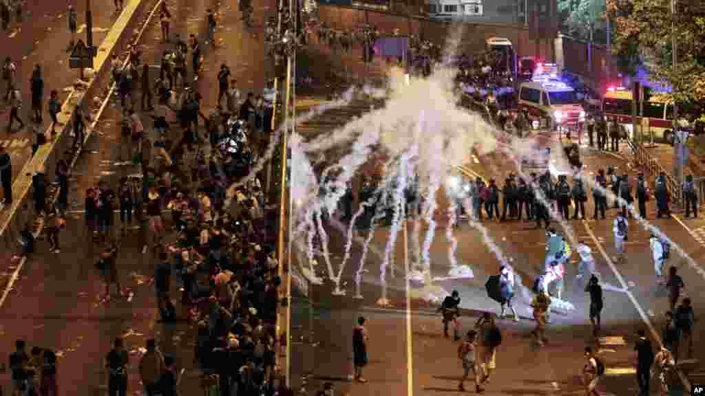 İğtişaş polisi Honq Konqda hökumət binasını mühasiərəyə almış izdihama qarşı gözyaşardıcı qazdan istifadə edir. 29 sentyabr, 2014.
