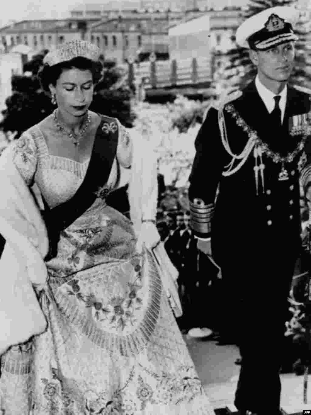 Queen Elizabeth and the Duke of Edinburgh enter Parliament House, Wellington, New Zealand, January 12, 1954. The Queen wears her coronation gown, the order of the garter, and a diamond tiara. (AP)