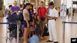 Polisi Mesir memeriksa dokumen para wisatawan Inggris di bandara Sharm el-Sheikh, Sinai selatan, Mesir (6/11).