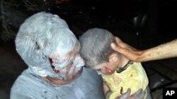 在叙利亚的伊德利卜省,一场空袭过后,一位受了伤的男子抱着自己受了伤的儿子