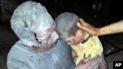 2013年4月25日在敘利亞伊德利卜西北部的的一個城鎮受到空襲後,一名受傷的敘利亞人手抱他受傷的兒子。