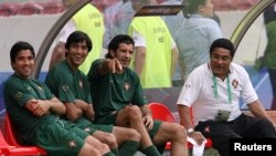 Portugal's Luis Figo (2nd R) gestures as he talks with former soccer star Eusebio (R) and team mates Deco (L) and Paulo Ferreira during the World Cup soccer training session in Stuttgart stadium, July 7, 2006.