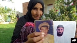 """The mother of former Guantanamo detainee Obiadullah holds pictures of her son, in Haiderkhil, Khost province, Afghanistan, Aug. 16, 2016. The case files of Afghan detainees at Guantanamo were """"full of mistakes,"""" a researcher with the Afghanistan Analysts Network says."""