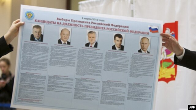 Russian election officials hold an election poster showing the candidates.