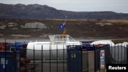 Les drapeaux des Îles Falkland devant un dépôt des machines et de matériel utilisé dans l'exploration pétrolière est vu à Port Stanley, 13 mars 2012.