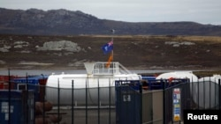 FILE - The Falkland Islands flag blows in the wind at a depot for machinery and equipment used in oil exploration at Port Stanley.