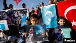 在2019年12月14日土耳其伊斯坦布尔一个反对中国的抗议中,几个维吾尔族少年举着印有英国足球俱乐部阿森纳球星梅苏特照片的宣传品。