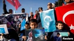 在2019年12月14日土耳其伊斯坦布爾一個反對中國的抗議中,幾個維吾爾族少年舉著印有英國足球俱樂部阿森納球星梅蘇特照片的宣傳品。