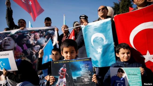 在土耳其伊斯坦布尔一个反对中国的抗议活动中,几个维吾尔族少年举着印有英国足球俱乐部阿森纳球星梅苏特照片的海报。(2019年12月14日)