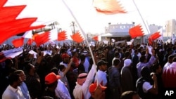 Bahraini anti-government protesters wave national flags and signs calling for regime change, March 2, 2011, outside the main police headquarters in the capital of Manama
