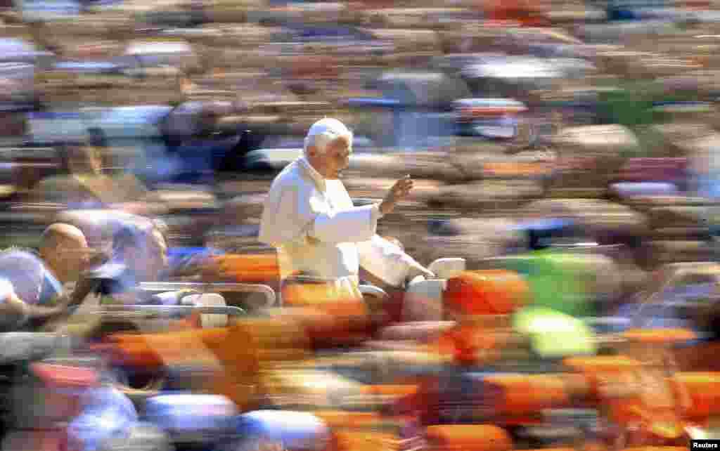 پاپ بندیکت در حال دست تکان دادن به جمعیت در میدان سنت پیترز در واتیکان، ۱۸ آوریل ۲۰۱۲