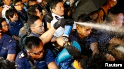 Police use pepper spray as they clash with pro-democracy protesters at an area near the government headquarters building in Hong Kong early October 16, 2014.