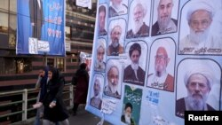 Women walk past electoral posters for the upcoming elections in central Tehran, Iran, Feb. 24, 2016.