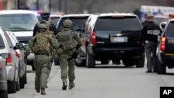 Polisi dan pasukan keamanan melakukan pencarian di jalan Main, kota Herkimer, negara bagian New York untuk mencari tersangka penembakan yang menewaskan 4 orang, Rabu (13/3).