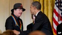 美國總統奧巴馬頒發肯尼迪中心終身成就獎予其中一名得獎者卡洛斯.桑塔納。