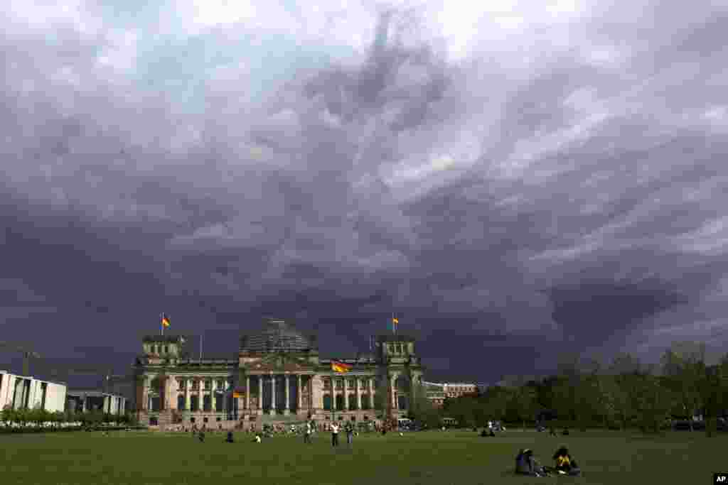 Dark clouds hang over the Reichstag, the German parliament Bundestag building, in Berlin.