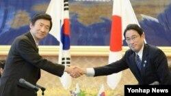윤병세 한국 외교부 장관과 기시다 후미오 일본 외무상이 지난 6월 열린 한일 외교장관 회담에 앞서 악수하고 있다.(자료사진)