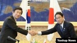윤병세 한국 외교부 장관(왼쪽)과 기시다 후미오 일본 외무상이 21일 도쿄의 외무성 이이쿠라 공관에서 열린 한일 외교장관 회담에 앞서 악수하고 있다.