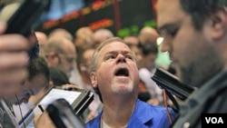 Pialang di Bursa Komoditas New York, Senin (14/3). Bencana gempa dan tsunami di Jepang mendorong harga minyak turun ke bawah 100 dolar per barel untuk pertama kalinya bulan ini.