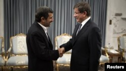 Turkey's Foreign Minister Ahmet Davutoglu (R) shakes hands with Iranian President Mahmoud Ahmadinejad before an official meeting in Tehran, January 5, 2012.