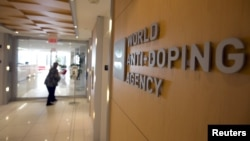FILE - A woman walks into the head office for the World Anti-Doping Agency (WADA) in Montreal, Nov. 9, 2015.