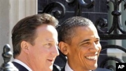 ປະທານາທິບໍດີບາຣັກ ໂອບາມາແຫ່ງສະຫະລັດ ( ຢືນເບື້ອງຂວາ) ຈັບຍມືກັບທ່ານ Cameron ນາຍົກລັດຖະມົນຕີອັງກິດ ວັນທີ 25 ພຶດສະພາ 2011