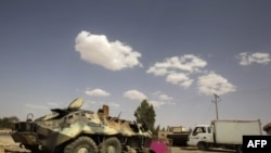 Xe thiết giáp của binh sĩ của ông Gadhafi bị hư vì oanh kích được bỏ nằm bên ngoài làng al-Qawalish