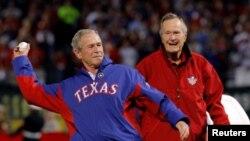 老布殊看著小布殊在德州為一場棒球賽象徵性發球(路透社2010年10月31日)