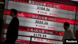Warga melewati papan yang memperlihatkan kejatuhan indeks-indeks saham China, di Hong Kong (25/8). (Reuters/Bobby Yip)