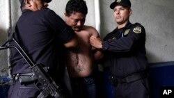 Un presunto pandillero de la banda Mara Salvatrucha es detenido por la policía en San Salvador.