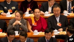 FILE - Gyaltsen Norbu, the Chinese government-appointed 11th Panchen Lama, center, sits with fellow delegates before the closing ceremony of the Chinese People's Political Consultative Conference (CPPCC) at the Great Hall of the People in Beijing, March 13, 2015.