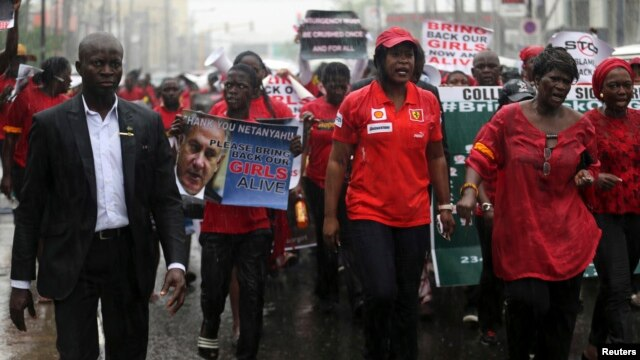 People walk in the rain during a protest for the release of secondary school girls abducted in the remote village of Chibok, along a road in Lagos, May 14, 2014.