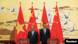 FILE - Chinese Premier Li Keqiang with Vietnamese Prime Minister Nguyen Xuan Phuc (L) attend a signing ceremony at the Great Hall of the People in Beijing, China.