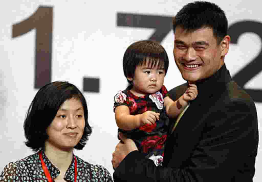 Yao Ming sostiene a su hija Qin Lei, junto a su esposa Ye Li, en la conferencia de prensa en la que anuncia su retiro del baloncesto.