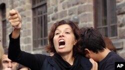 Emel Kitapci, esposa de una de las víctimas de los ataques del sábado reacciona junto a su hijo, Artun Siyah Kitapci, de 11 años, durante una manifestación en el sitio de las explosiones en Ankara, Tuquía, el lunes, 12 de octubre de 2015.