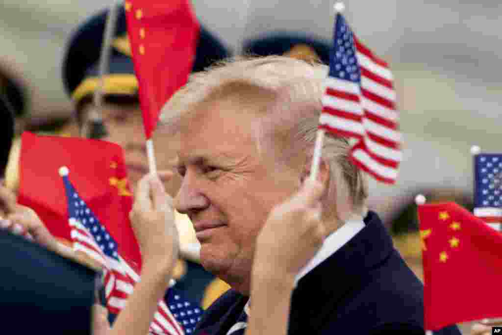 Children wave U.S. and Chinese flags as President Donald Trump arrives at Beijing Airport, Nov. 8, 2017.