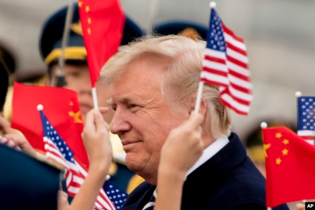 Children wave U.S. and Chinese flags as President Donald Trump arrives at Beijing Airport, Wednesday, Nov. 8, 2017, in Beijing, China.