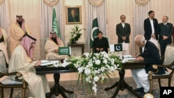 Visiting Saudi Arabia's Crown Prince Mohammed bin Salman, center left, and Pakistani Prime Minister Imran Khan, center right, witness the signing ceremony of the Memorandum of Understanding (MOU) on Petroleum, in Islamabad, Pakistan, Sunday, Feb. 17, 2019.