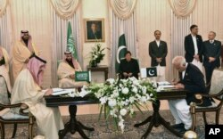 Saudi Arabia's Crown Prince Mohammed bin Salman, center left, and Pakistani Prime Minister Imran Khan, center right, witness the signing ceremony of the Memorandum of Understanding (MOU) on Petroleum, in Islamabad, Pakistan, Feb. 17, 2019.