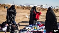 Para perempuan membongkar baju-baju bekas di luar kamp al-Hol, tempat pengungsian keluarga mantan kombatan ISIS, di wilayah al-Hasakeh, timur laut Suriah, pada 14 Januari 2020. (Foto: AFP)