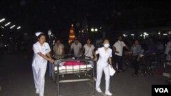 Para perawat membantu evakuasi pasien dari rumah sakit Chiang Rai yang diguncang gempa di Thailand utara (24/3).