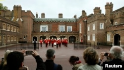 Royal fans wait outside St James's Palace before the christening of Prince George in London Oct. 23, 2013.
