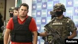 Marinir Meksiko mengawal Jesus Alfredo Guzman, alias El Gordo, saat diperlihatkan kepada media di Mexico City, 2012.