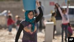 지난달 3일 시리아-터키 국경지역인 수르크 난민촌에서 코바니에서 피난한 쿠르드족 난민이 물동이를 이고 가고 있다. (자료사진)