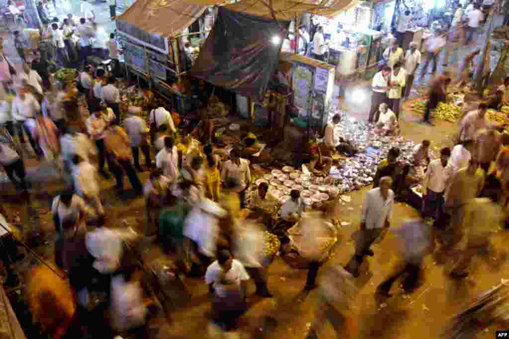 March 31: Vendors display as commuters walk past in Kolkata, India. (AP Photo/Bikas Das)