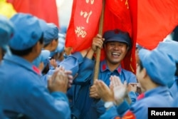 Participants dressed in replica Red Army uniforms welcome teammates as they return from a hike through the mountains during a Communist team-building course extolling the spirit of the Long March outside Jinggangshan, Jiangxi province, China, Sept. 14, 2017.