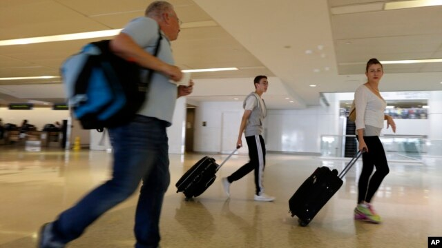 Dror Heitner, left, walks with his wife Rinat Heitner, right, and their 16-year-old son Ori Heitner toward a security checkpoint at Newark Liberty International Airport, July 22, 2014, in Newark, N.J.