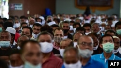People wearing face masks attend a meeting by Thai government officials discussing the economic impact of the COVID-19 coronavirus in the border area with Malaysia at Sungai Kolok town in Thailand's southern province of Narathiwat on September 12, 2020 as