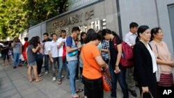 Myanmar people living in Thailand line up for early voting outside Myanmar Embassy in Bangkok, Thailand, Saturday, Oct. 17, 2015.