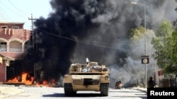 Sebuah kendaraan militer Tentara Irak dengan Pasukan Mobilisasi Rakyat Syi'ah (PMF) bertempur dengan militan Islam di Tal Afar, Irak, 26 Agustus 2017. (REUTERS/Thaier Al-Sudani)
